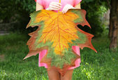 Girl holding decorative maple leaf in park — Stock Photo