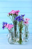 Beautiful summer flowers in vases on blue wooden background — Stock Photo
