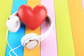 Headphones and hearts on wooden background — Stock Photo