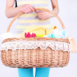 Woman holding laundry basket with clean clothes, towels and pins, on gray background — Stock Photo #48450527