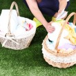 Woman holding laundry baskets with clean clothes, towels and pins, on green grass background — Stock Photo #48450529