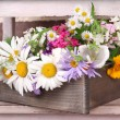 Beautiful flowers in crate on small ladder on brick wall background — Stock Photo #48452279