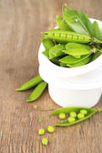 Fresh green peas in bowl on wooden table — Stock Photo