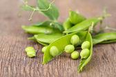 Fresh green peas on wooden table — Stock Photo