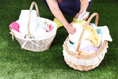 Woman holding laundry baskets with clean clothes, towels and pins, on green grass background — Stock Photo