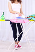Woman ironing clothes on ironing board, close-up, on light background — Stock Photo