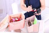Girl applying make up on home interior background — Stock Photo