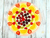 Homemade sweet pizza with fruits on wooden table, close up — Stock Photo