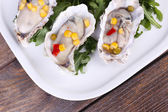 Tasty cooked oysters in shell on wooden table — Stock Photo