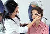 Młoda kobieta stylista robi makijaż piękna dziewczyna w gabinecie kosmetycznym — Zdjęcie stockowe