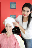 Young woman hairdresser and client in beauty salon — Zdjęcie stockowe