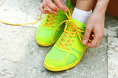 Young woman tying shoelace outside — Stock Photo
