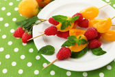 Fresh fruit kebabs for healthy snack on plate close up — Stock Photo