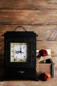 Old retro clock on wooden background — Stock Photo