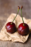 Sweet cherries with chocolate, on wooden background — Stock Photo