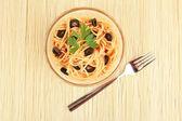 Italian spaghetti in plate on bamboo mat — Stock Photo