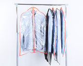 Office male clothes in cases for storing on hangers — Stock Photo