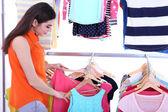 Junge frau wählen sie kleidung in der nähe von rack mit laschen — Stockfoto