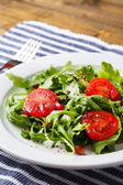 Green salad made with  arugula, tomatoes and sesame on plate — Stock fotografie