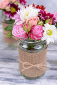 Beautiful bouquet of bright flowers in jars on table — Stock Photo