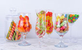 Different colorful fruit candy in glasses on table — Stock Photo
