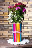 Beautiful flowers in colorful pencils vase — Stockfoto