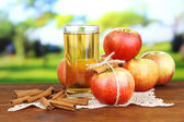 Ripe apples with with cinnamon sticks and glass of  apple drink — Stock Photo