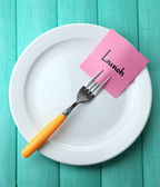 Note paper with message  attached to fork, on plate — Stock Photo