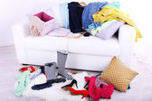 Messy colorful clothing on sofa — Stock Photo