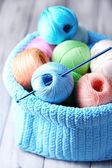 Colorful clews, napkin and crochet hook in basket — Stock Photo
