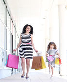 Happy mom and daughter with shop bags, outdoors — Stock Photo