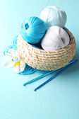 Colorful clews and crochet hooks in wicker basket — Stock Photo