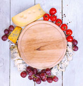 Different types of cheese with empty board — Stock Photo