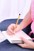 Closeup of young female student sitting on floor and studying — Stock Photo