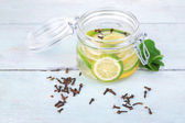Pickled limes and cloves in glass jar — Stock Photo