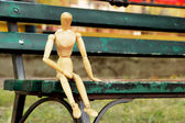 Wooden pose puppet sitting on bench — Stock Photo