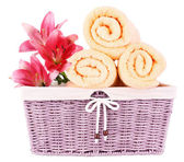 Color towels and lily flowers in wicket basket — Stock Photo