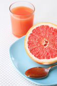 Half of grapefruit, glass of fresh juice and spoon on plate — Stock Photo