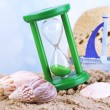 Hourglass in sand on blue sky background — Stock Photo #48714271