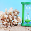 Hourglass in sand on blue sky background — Stock Photo #48714275