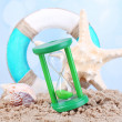 Hourglass in sand on blue sky background — Stock Photo #48714277