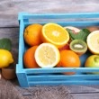 Fresh exotic fruits with green leaves in wooden box — Stock Photo #48714485