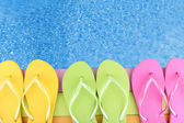Colored flip flops on wooden platform beside sea — Стоковое фото