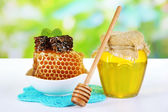 Sweet honeycombs in bowl and bank with honey on wooden table — Stock fotografie