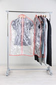 Office female clothes in cases for storing on hangers — Stock Photo