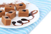 Many toffee on plate on napkin — Stock Photo