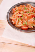 Pasta with tomato sauce on plate on table — Stock Photo
