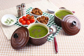 Tasty soup in saucepans on tablecloth — Stock Photo