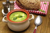 Tasty soup in saucepan on wooden table — Stock Photo