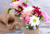 Beautiful bouquet of bright flowers in jars — Stock Photo